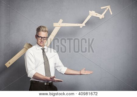 Concept: Positive business outlook. Happy confident businessman presenting or pointing at empty space below business graph with upward trend, isolated on grey background.