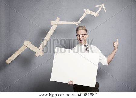 Concept: Promising business development. Cheering happy businessman holding empty panel in front of ascending business graph and pointing up, isolated on grey background.