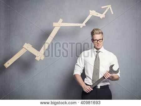 Concept: Building your own successful career or business. Young confident businessman holding  wrench in front of business graph with positive trend, isolated on grey background.