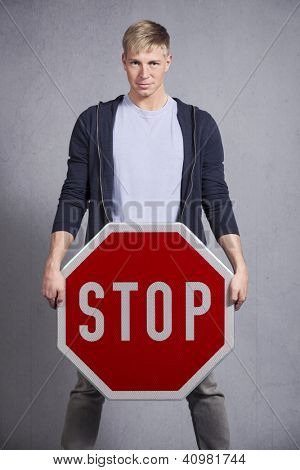 Friendly man holding stop sign isolated on grey background.