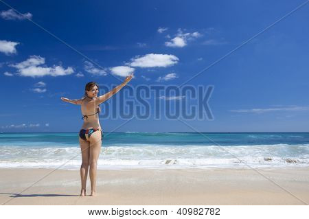 Beautiful young woman with arms open in a tropical beach enjoying the summer