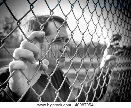 Upset Man Holding Chain Fence Barrier