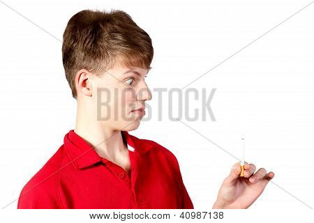 Teen Boy Looks At A Cigarette
