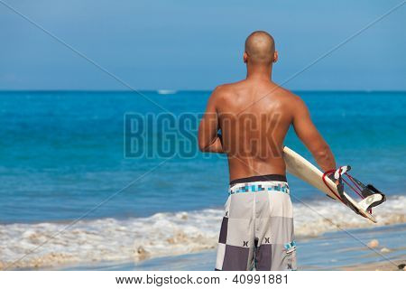 young man with surfboard on beach in Bali