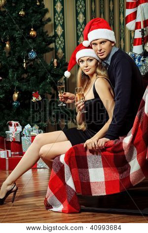 Happy young couple celebrating Christmas near the Christmas tree and fireplace at home.