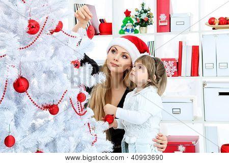 Porträt einer glücklichen Mutter mit ihrer Tochter schmücken Weihnachtsbaum zu Hause.
