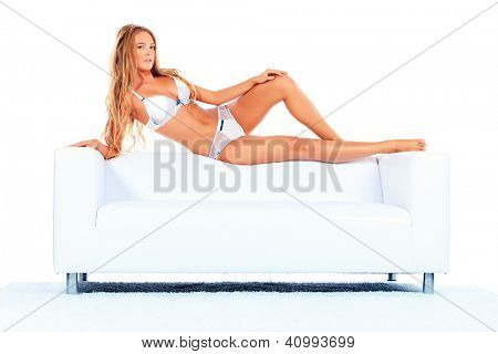 Portrait of a sexual woman in white lingerie lying on a white sofa.