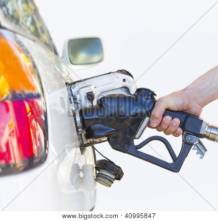 A Hand Fueling White Car.