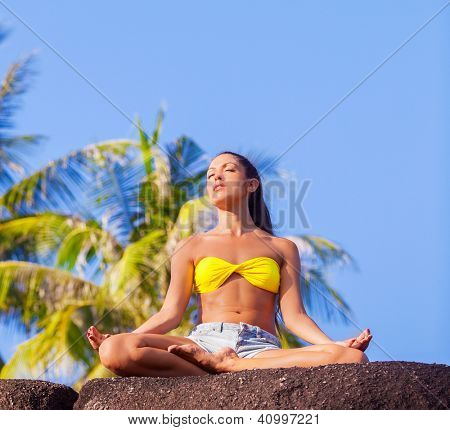 beautiful young woman practicing yoga outdoor at the tropical resort