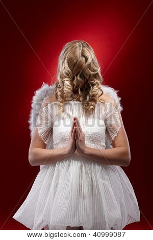 Faceless angel praying over red background.