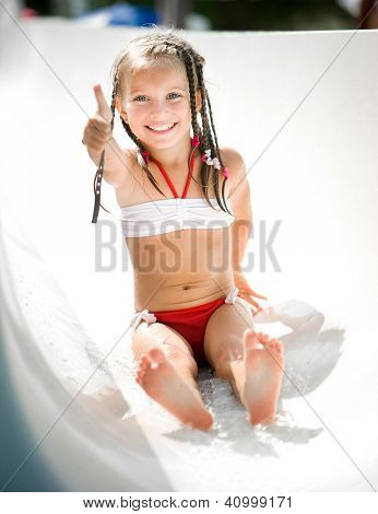 Little girl on water slide at aquapark show the thumb