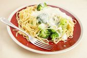 A plate of linguine pasta mixed with boiled broccoli and topped with cheese sauce and parmesan