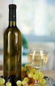 White wine in glass with bottle on salver on room background