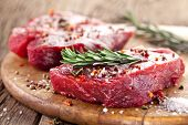 foto of bloody  - Raw beef steak on a dark wooden table - JPG