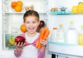 stock photo of refrigerator  - girl with carrots on background refrigerator - JPG