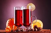 mulled wine in the glasses, spice and orange on wooden table on purple background