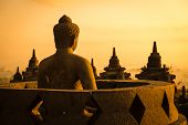 stock photo of buddha  - Buddha statue in open stupa in Borobudur or Barabudur temple Jogjakarta Java Indonesia at sunrise - JPG