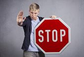 image of disapproval  - Serious man showing stop gesture with hand as warning while holding stop sign isolated on grey background - JPG