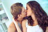 stock photo of amor  - Young affectionate couple kissing tenderly - JPG