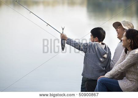 Boy admiring fishing catch with family at lake