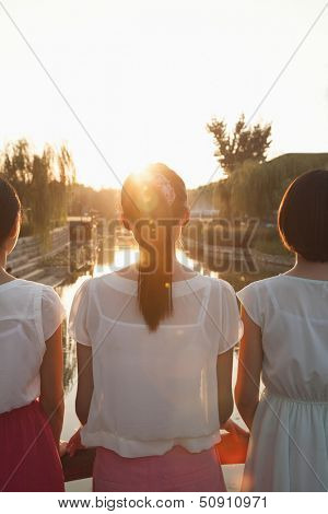 Three Young Women Looking Downstream at a Sunset