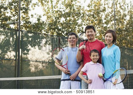 Family playing tennis, portrait