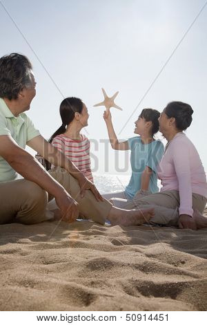 Multi generational family sitting on the beach looking at starfish