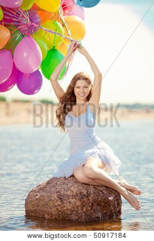 Beautiful young stylish woman with ainbow balloons in hands against the sky. Positive girl on nature. Smiling woman outdoors enjoying.