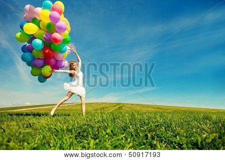 Mulher feliz aniversário contra o céu com balões de ar cor de arco-íris nas mãos. ensolarado e positivo