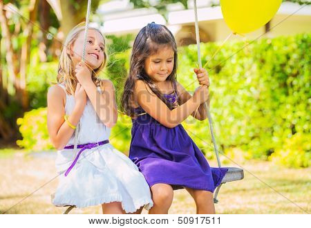 Happy little Girls Playing on Swing