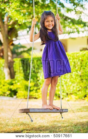 Cute Little Girl Playing on Swingset