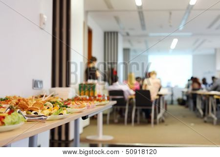 Table with cold snacks and refreshments for business meeting. Focus on food.