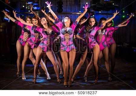 Nine beautiful showgirls in purple costumes with raised hands perform on stage