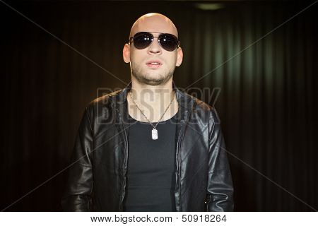 A man in a leather jacket with sunglasses with a pendant around his neck