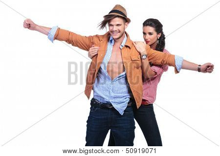 young casual couple posing in the titanic pose with the woman behind and the man holding his hands wide open and smiling. on white background
