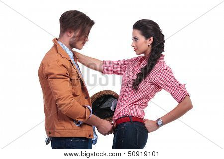 side view of a young casual couple looking at eachother while the man is undoing her belt while she is holding her hand on his shoulder. on white background