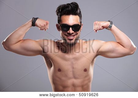 topless young man smiling for the camera while bragging with his arm muscles. on gray background