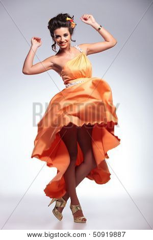 full length portrait of a young fashion woman dancing and looking into the camera while revealing beautiful legs. on gray background