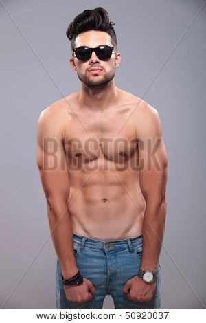topless young man flexing his muscles while looking into the camera. on gray background