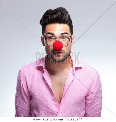 closeup of a young fashion man looking emotionless at the camera while wearing a red nose. on a light background