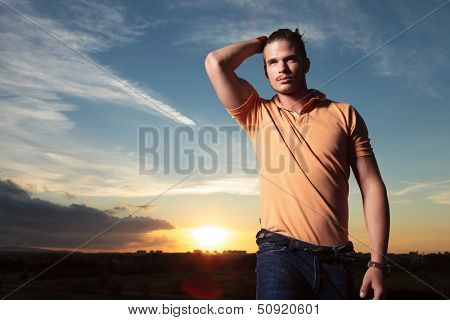 young casual man outdoor passing a hand through his hair while looking away from the camera with the sunset behind him