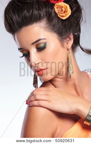 closeup portrait of a young fashion woman with her hand on her shoulder, looking over at her back. on gray background