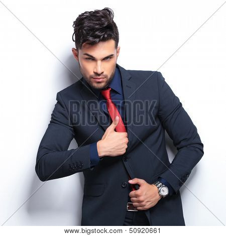 elegant young fashion man in tuxedo pretending to pull a gun out of his jacket. on gray background