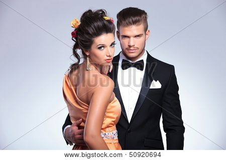 young fashion couple embracing while woman looks into the camera over her shoulder. on gray background