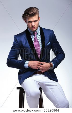closeup portrait of a young business man sitting on a chair and taking his suit jacket off while looking into the camera. on a gray background