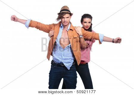 young casual couple looking into the camera while standing in the titanic pose with the woman behind holding the man while he has his arms wide open. on white background