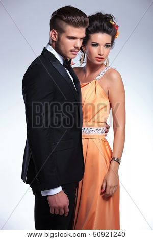 young fashion couple looking away from the camera. on gray background