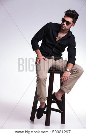 full length portrait of a young fashion man sitting on a chair and looking at his side, away from the camera while holding his elbow on his leg. on a light background