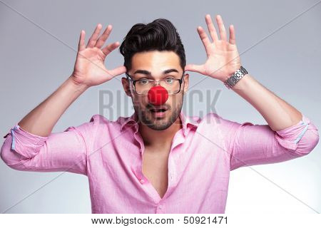 young fashion man with a red nose acting crazy, holding his palms at his head like antlers while looking at the camera. on a light background