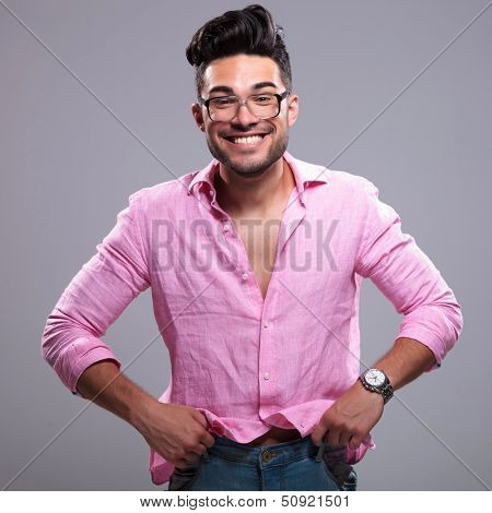 young fashion man pulling his pants up with a silly smile on his face. on a gray background